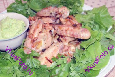 В центр блюда горкой выложить готовые куриные крылышки. Рядом поставить соусник и разложить листья салата.