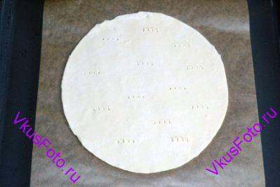 Круг теста положить на противень с бумагой, наколоть вилкой в нескольких местах.