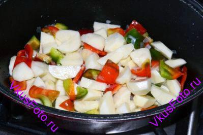 К луку положить сладкий перец и картофель. Влить 200 мл воды и довести до кипения.