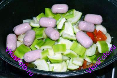 Добавить сосиски очищенные от оболочки. Через 5 минут снять кастрюлю с плиты.