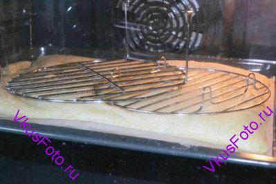 Духовку предварительно разогреть до 190 градусов. Поставить противень в духовку. Через 5 минут накрыть выпекаемый корж решеткой, чтобы остановить поднятие теста.