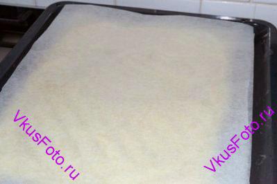 Еще через 10 минут вынуть противень из духовки. Нужно перевернуть выпекаемый корж. Для этого накрыть корж другим листом пекарской бумаги.