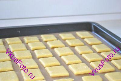 Нарезать на квадраты по 3,5-4 см с каждой стороны.  Переложить квадраты на противень с бумагой.