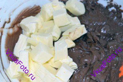 В большой миске на водяной бане растопить шоколад, периодически помешивая.  Когда шоколад полностью раствориться, снять миску с плиты и положить размягченное масло нарезанное кубиками. Перемешать массу до однородности.