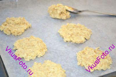 С помощью чайной ложки выложить кусочки теста на противень с пекарской бумагой. На одно печенье нужно брать тесто величиной чуть больше величины грецкого ореха. Между печеньями нужно оставлять несколько см, так как во время выпечки тесто немного расплывается.