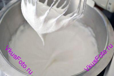 В два этапа добавить сахар, постоянно взбивая белки. Белки взбивать пока они не станут блестящими и плотными как для безе.