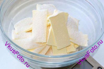 Сливочное масло должно быть комнатной температуры. Нарезать его кусочками и всыпать сахар. Масло взбить вместе с сахаром до пушистого состояния.
