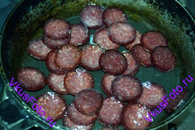 На сковороде разогреть 1 ст.л. оливкового масла и обжарить на ней ломтики колбасы.