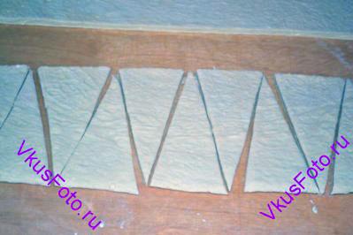 Тесто разрезать вдоль пополам. Из каждой полосы нарезать треугольники. Основание должно быть 9 см, а стороны по 15 см.