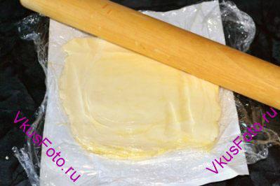 Развернуть пачку холодного сливочного масла, но бумагу не убирать. Накрыть масло пищевой пленкой и, осторожно постукивая скалкой, придать маслу форму квадрата толщиной 1 см.
