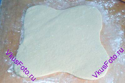 Поднявшееся тесто осторожно выложить на доску и раскатать в четыре стороны, начиная от центра.