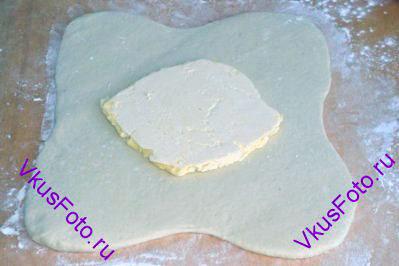 В центр раскатанного теста положить пласт сливочного масла.