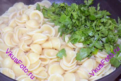 Туда же положить макароны и крупно нарезанную петрушку, влить немного отвара от макарон.