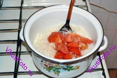 В пустую кастрюлю налить 250 мл кипятка, положить рис и 2/3 помидоров. Рис доварить, постоянно помешивая и добавляя горячую воду. Приблизительно понадобится 350-500 мл кипятка.