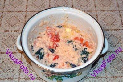 Когда рис будет готов, снять кастрюлю с огня. Добавить сливочное масло, крупные листья базилика, запеченный сыр и оставшиеся помидоры.