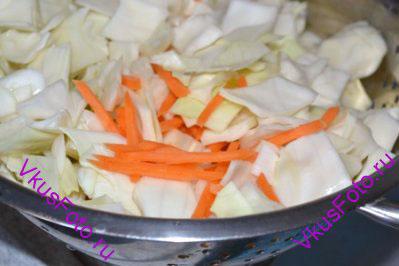 Положить капусту и морковь в миску и залить крутым кипятком. Сразу же откинуть овощи на дуршлаг и дать стечь воде.