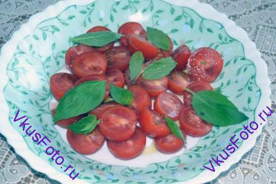 Поверх томатов разложить листья базилика.