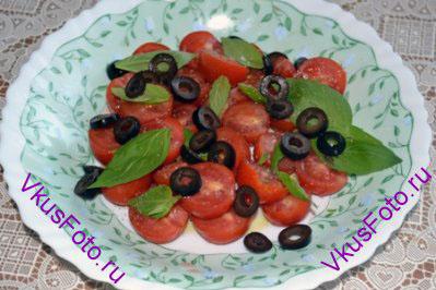 Маслины без косточки нарезать колечками и положить на блюдо поверх томатов и базилика.