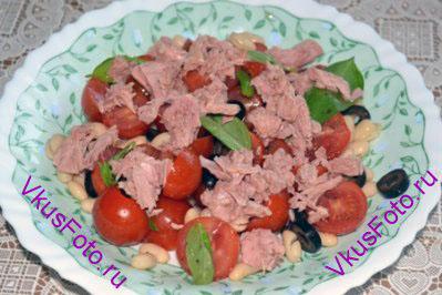 Слить жидкость у консервированного тунца. Вилкой разделить рыбу на кусочки и положить положить поверх салата.
