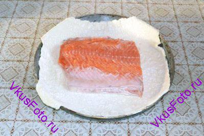Раскатать тесто по размеру филе плюс 5-7 см с каждого края. Тесто переложить на посыпанный мукой противень. В центр теста положить филе кожей вниз..
