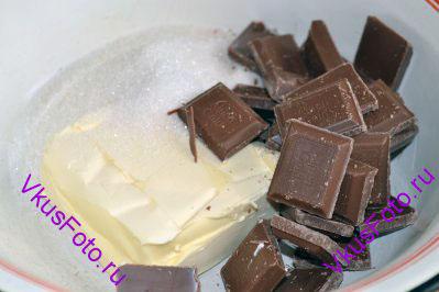 В миску положить сливочное масло, сахар и кусочки шоколада. Миску поставить на водяную баню и, постоянно помешивая, дождаться пока масло и шоколад не растают.