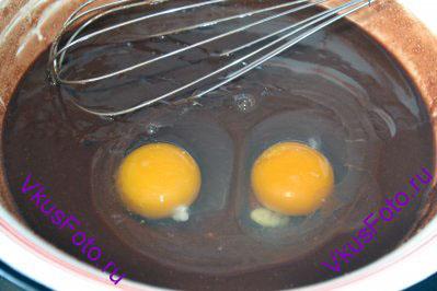 Масляно-шоколадную смесь немного остудить и добавить яйца. Взбить тесто венчиком.