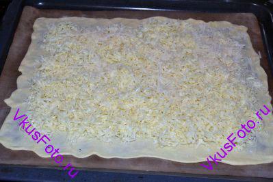 На тесто ровным слоем выложить сыр, оставляя края свободными. Они нам будут нужны чтобы защипать края лепешки.