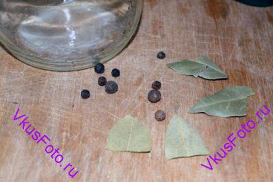 На дно стерилизованных банок положить горошину душистого перца, 3 горошины черного перца, половинку лаврового листа.