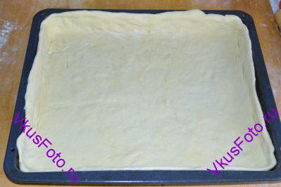 Разделить тесто на 2 части: побольше и поменьше. Если планируете делать украшение, то отдельно нужно оставить еще один небольшой кусочек теста. Большая часть пойдет на низ пирога. Раскатываем и кладем на смазанный маслом противень, оставляя бортики по краям.
