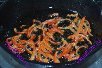 Когда почувствуется аромат, примерно через минуту, горошины душистого перца вынуть из масла и выбросить. Сразу же добавить нарезанный перец чили.