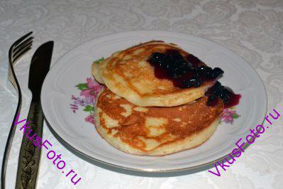 Готовые творожные блинчики положить в порционные тарелочки и полить вареньем.