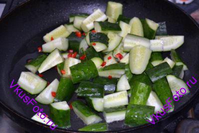 На сильно разогретую сковороду с маслом выложить огурцы и перец чили. Обжарить в течении 2-х минут, постоянно помешивая и встряхивая сковороду.