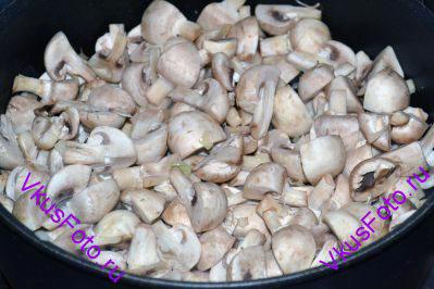 Добавить шампиньоны разрезанные на 4 части. Грибы жарить пока не испарится выделившаяся жидкость.