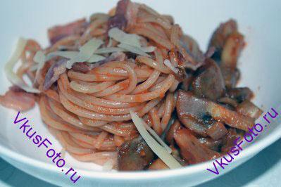 Горячие спагетти разложить по тарелкам. Украсить поджаренным беконом и пармезаном.