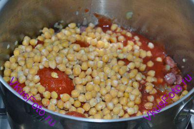 Добавить турецкий горох нут, жидкость сливаем. Добавить нарезанные томаты вместе с жидкостью.  <i>Если у вас нет консервированного гороха нут, то его можно отварить самим. На ночь 200 г гороха нут замачиваем в холодной воде. Утром воду слить и залить новой порцией воды, кастрюлю поставить на огонь. Варить нут до готовности примерно 1-1,5 часа, пока он не станет мягким. После варки воду слить.</i>