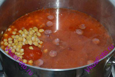 Влить в кастрюлю бульон, приправить солью и перцем. Варить суп из колбасок и турецкого гороха нут в течении 20 минут на слабом огне.
