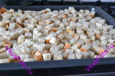 Выкладываем кубики хлеба на противень в один слой.