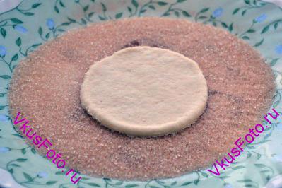 Берем кружочек теста и макаем его в коричный сахар.