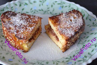 Горячие поджаренные бутерброды с шоколадом перекладываем на тарелку и обильно посыпаем сахарной пудрой.