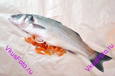 Рыбу положить на фольгу. Брюшко наполнить овощами.