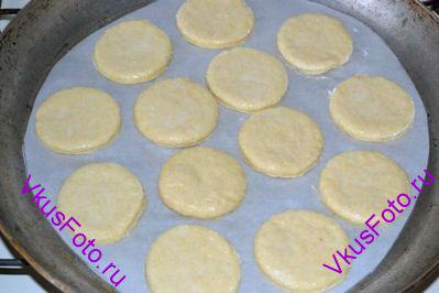 Сконы разложить на противень, выстланный бумагой для выпечки. Верх плюшек смазать оставшейся яично-молочной смесью.