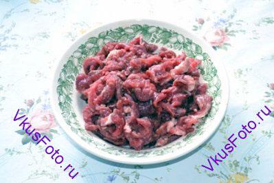 Мясо нарезать тонкими полосками примерно 0,7-4 см. Посолить и поперчить.
