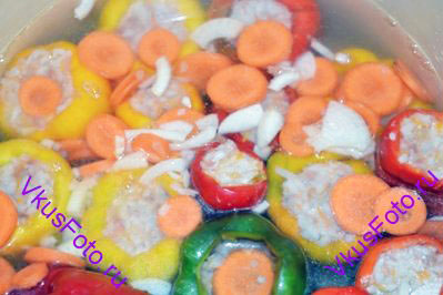 Покрыть перцы мясным бульоном. Положить нарезанные лук и морковь.
