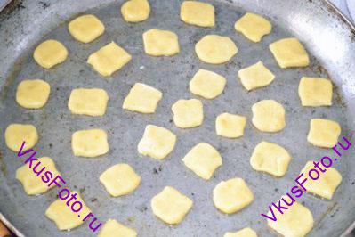 Тесто раскатать на тоненькие колбаски толщиной с большой палец, порезать на подушечки. Положить на смазанный маслом противень, оставляя большое расстояние между печеньями – они сильно увеличатся.