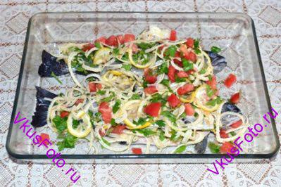 Нафаршировать рыбу овощной смесью, а оставшуюся часть выложить поверх рыбы.  Запекать в духовке 40 минут при температуре 200 градусов.