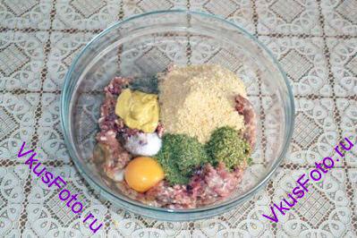 Крекеры измельчить до состояния крошки и положить в фарш. Добавить горчицу, травы, яйцо, соль и перец. Все хорошенько перемешать.