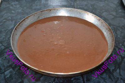 Перелить тесто в смазанную форму. Диаметр формы должен быть больше в 1,5 раза диаметры формы, в которой выпекался первый (светлый) корж.